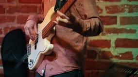 Ένα άτομο παίζει μια άσπρη βαθιά κιθάρα για μια απόδοση σε έναν φραγμό τζαζ, στα χέρια πλαισίων μόνο απόθεμα βίντεο