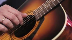 Ένα άτομο παίζει μια ακουστική κιθάρα Κινηματογράφηση σε πρώτο πλάνο του χεριού που χτυπά τις σειρές της κιθάρας απόθεμα βίντεο
