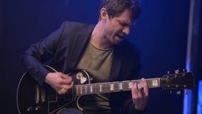 Ένα άτομο παίζει μια ηλεκτρική κιθάρα και τραγουδά σε ένα σκοτεινό δωμάτιο απόθεμα βίντεο