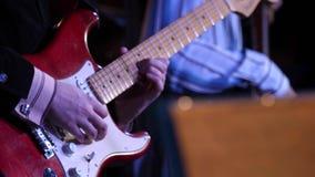 Ένα άτομο παίζει την κιθάρα στη σκηνή Παιχνίδι νεαρών άνδρων στην ηλεκτρική κινηματογράφηση σε πρώτο πλάνο κιθάρων Ηλεκτρική ενέρ απόθεμα βίντεο