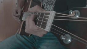 Ένα άτομο παίζει το α σόλο σε μια ακουστική κιθάρα φιλμ μικρού μήκους