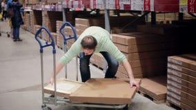 Ένα άτομο παίρνει ένα κιβώτιο από το ράφι, βάζοντας το στο καροτσάκι, που ελέγχει τον κατάλογό του σε μια αποθήκη εμπορευμάτων απ απόθεμα βίντεο