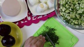 Ένα άτομο παίρνει ένα αγγούρι από ένα πιάτο, και αρχίζει το σε έναν τέμνοντα πίνακα φιλμ μικρού μήκους