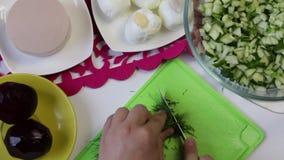 Ένα άτομο παίρνει ένα αγγούρι από ένα πιάτο, και αρχίζει το σε έναν τέμνοντα πίνακα απόθεμα βίντεο
