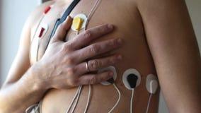 Ένα άτομο παίρνει δικών του παραδίδει την καρδιά στεμένος στους αισθητήρες του holter HD απόθεμα βίντεο