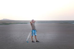 Ένα άτομο περπατά κατά μήκος της ακτής της λίμνης με τον πίνακα σαλαχιών Μια αλατισμένη ακτή λιμνών Ένα Σόλτ Λέικ Στοκ Φωτογραφία