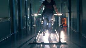 Ένα άτομο περπατά σε μια διαδρομή, χρησιμοποιώντας τη ρομποτική ορθοπεδική συσκευή σε μια κλινική 4K φιλμ μικρού μήκους