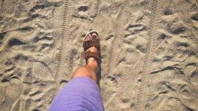 Ένα άτομο περπατά στις πτώσεις κτυπήματος στην άμμο κοντά στη θάλασσα φιλμ μικρού μήκους