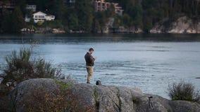 Ένα άτομο πετά τον κηφήνα του πέρα από τον ωκεανό στο πάρκο Whytecliff , Δυτικό Βανκούβερ απόθεμα βίντεο