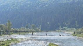 Ένα άτομο πηγαίνει πέρα από τον ποταμό βουνών σε μια γέφυρα απόθεμα βίντεο
