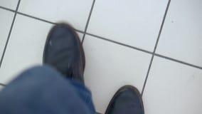 Ένα άτομο πηγαίνει στην υπεραγορά Τοπ άποψη σχετικά με τα πόδια στα τζιν και τις βρώμικες μπότες S απόθεμα βίντεο