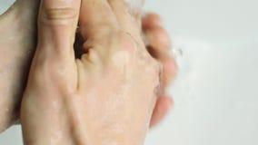 Ένα άτομο πλένει τα χέρια του κάτω από τη στρόφιγγα στο λουτρό απόθεμα βίντεο
