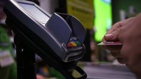 Ένα άτομο πληρώνει από την πιστωτική κάρτα μέσω του τερματικού στο κατάστημα HD, 1920x1080, σε αργή κίνηση φιλμ μικρού μήκους