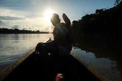 Ένα άτομο πλοηγεί τον ποταμό Javari σε μια βάρκα στοκ φωτογραφίες