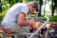 Ένα άτομο που αισθάνεται τον πόνο στο γόνατό του κατά τη διάρκεια του αθλητισμού και workout στο π στοκ εικόνες