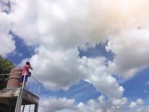 Ένα άτομο που αναρριχείται μέχρι τη φωτογραφία στον ουρανό πρωινού με ένα χνουδωτό άσπρο σύννεφο στοκ φωτογραφία