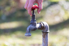 Ένα άτομο που ανοίγει μια στρόφιγγα με το νερό υπηρεσιών Στοκ εικόνα με δικαίωμα ελεύθερης χρήσης
