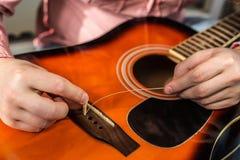 Ένα άτομο που αλλάζει τις παλαιές σχισμένες σειρές κιθάρων στην ακουστική κιθάρα Στοκ Φωτογραφία