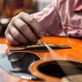 Ένα άτομο που αλλάζει τις παλαιές σχισμένες σειρές κιθάρων στην ακουστική κιθάρα Στοκ Εικόνες
