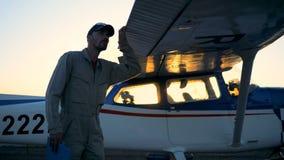 Ένα άτομο που εξετάζει biplane σε ένα υπόβαθρο ηλιοβασιλέματος, κλείνει επάνω φιλμ μικρού μήκους