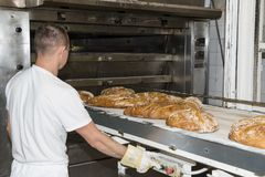 Ένα άτομο που εργάζεται με έναν βιομηχανικό φούρνο σε ένα αρτοποιείο Στοκ Φωτογραφία
