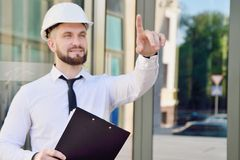 Ένα άτομο που εργάζεται σε ένα άσπρο κράνος και ένα άσπρο πουκάμισο με μια ταμπλέτα μέσα στοκ φωτογραφία με δικαίωμα ελεύθερης χρήσης