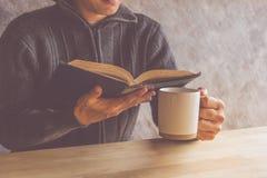 Ένα άτομο που διαβάζει ένα βιβλίο με την κατανάλωση του καφέ ή του τσαγιού Στοκ Φωτογραφία