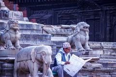 Ένα άτομο που διαβάζει μια εφημερίδα σε Bhaktapur Στοκ Εικόνες