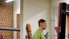 Ένα άτομο που κάνει έναν Τύπο πάγκων με τους αλτήρες που κάθεται με ένα ευθύ πιάσιμο σε ένα στούντιο ικανότητας απόθεμα βίντεο