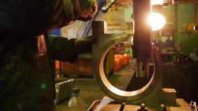 Εγκαταστάσεις κατασκευής Ένα άτομο που κάνει τη χειρωνακτική λείανση με μια μεγάλη λεπτομέρεια σιδήρου απόθεμα βίντεο