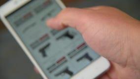 Ένα άτομο που κοιτάζει και επιλέγει τα όπλα που αγοράζουν στην περιοχή απόθεμα βίντεο