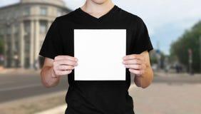 Ένα άτομο που κρατά ένα άσπρο φύλλο του εγγράφου Κράτημα ενός βιβλιάριου o Το υπόβαθρο της πόλης στοκ φωτογραφίες με δικαίωμα ελεύθερης χρήσης