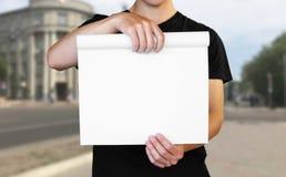 Ένα άτομο που κρατά ένα άσπρο φύλλο του εγγράφου Κράτημα ενός βιβλιάριου o Το υπόβαθρο της πόλης στοκ εικόνες