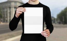 Ένα άτομο που κρατά ένα άσπρο φύλλο του εγγράφου Κράτημα ενός βιβλιάριου o Το υπόβαθρο της πόλης στοκ φωτογραφία