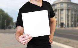Ένα άτομο που κρατά ένα άσπρο φύλλο του εγγράφου Κράτημα ενός βιβλιάριου o Το υπόβαθρο της πόλης στοκ φωτογραφία με δικαίωμα ελεύθερης χρήσης