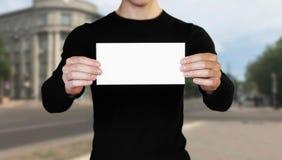 Ένα άτομο που κρατά ένα άσπρο φύλλο του εγγράφου Κράτημα ενός βιβλιάριου o Το υπόβαθρο της πόλης στοκ εικόνα με δικαίωμα ελεύθερης χρήσης