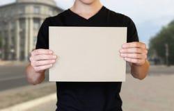 Ένα άτομο που κρατά ένα κομμάτι του χαρτονιού στα χέρια του Κράτημα ενός βιβλιάριου o Το υπόβαθρο της πόλης στοκ φωτογραφία με δικαίωμα ελεύθερης χρήσης