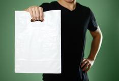 Ένα άτομο που κρατά μια άσπρη πλαστική τσάντα κλείστε επάνω Απομονωμένος στην πράσινη ανασκόπηση στοκ εικόνες με δικαίωμα ελεύθερης χρήσης