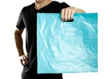 Ένα άτομο που κρατά μια τυρκουάζ πλαστική τσάντα κλείστε επάνω η ανασκόπηση απομόνωσε το λευκό στοκ φωτογραφία με δικαίωμα ελεύθερης χρήσης
