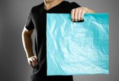 Ένα άτομο που κρατά μια τυρκουάζ πλαστική τσάντα κλείστε επάνω Απομονωμένος στην γκρίζα ανασκόπηση στοκ φωτογραφία