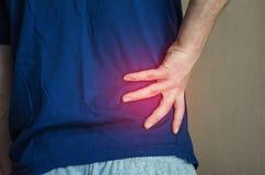 Ένα άτομο που κρατά την πλάτη του Πόνος στην πλάτη στοκ φωτογραφία