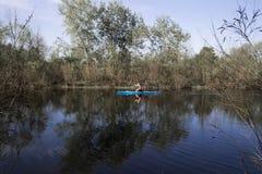 Ένα άτομο που κωπηλατεί σε ένα μπλε καγιάκ σε έναν ποταμό μεταξύ των παχιών αλσυλλίων Στοκ φωτογραφία με δικαίωμα ελεύθερης χρήσης