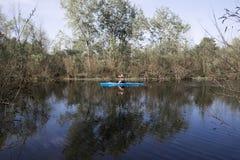 Ένα άτομο που κωπηλατεί στο καγιάκ σε έναν ποταμό μεταξύ των αλσυλλίων των δέντρων Στοκ Εικόνες