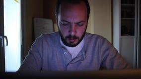 Ένα άτομο που μελετά/που ψάχνει κάτι στον Ιστό στο δωμάτιο μελέτης Γράφει κάτι στο πληκτρολόγιο και φαίνεται κουρασμένος φιλμ μικρού μήκους