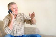 Ένα άτομο που μιλά στο τηλέφωνο, η συγκίνηση μιας καλής διάθεσης στο πρόσωπό του στοκ εικόνες