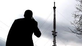 Ένα άτομο που μιλά στο τηλέφωνο στο υπόβαθρο έναν τηλεφωνικό πύργο, ένας κινητός έλεγχος δικτύων απόθεμα βίντεο