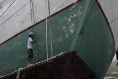 Ένα άτομο που ξαναβάφει την ξύλινη βάρκα στοκ φωτογραφία με δικαίωμα ελεύθερης χρήσης