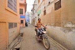 Ένα άτομο που οδηγά ένα μηχανικό δίκυκλο μέσω των στενών παρόδων Στοκ Φωτογραφία