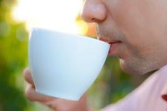 Ένα άτομο που πίνει τον καυτό καφέ από το φλυτζάνι Στοκ εικόνα με δικαίωμα ελεύθερης χρήσης