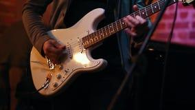 Ένα άτομο που παίζει masterfully την κιθάρα για μια απόδοση σε έναν φραγμό τζαζ, στο πλαίσιο των χεριών ατόμων ` s απόθεμα βίντεο